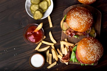 Burger and french fries on wooden table.