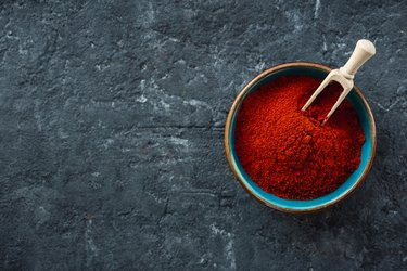 Chili pepper powder on dark background copy space top view