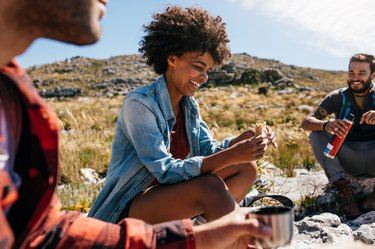 Woman with friends eating hiking snacks taking a break during hike