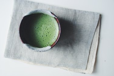 Bowl of Matcha green tea prepared in traditional ceremonial manner, high angle view.