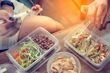 People eating from meal prep containers
