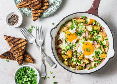 Potatoes, ham, eggs breakfast hash in a frying pan on a light background, top view. Delicious, nutritious breakfast, snack