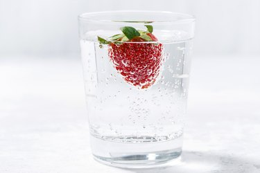 glass of carbonated water with fresh strawberries