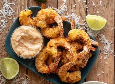 Air Fryer Coconut Shrimp on plate with orange dipping sauce and lime