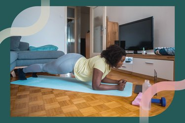 Woman participating in the plank challenge in her living room by doing a forearm plank while following a video on her laptop