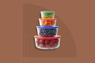 A stack of four Pyrex containers storing different fruit and vegetables