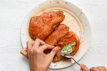A hand uses a spoon to stuff a broccoli-cheese mixture into a seasoned chicken breast