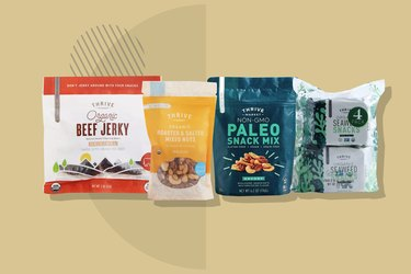A Thrive Market Snack Kit, including beef jerky, salted nuts, paleo snack mix and seaweed crisps displayed on a beige background