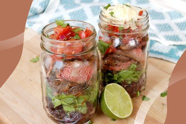 Steak Burrito Jar on wooden table with blue kitchen towel and lime