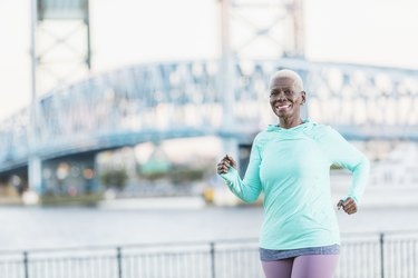 woman in teal shirt and purple leggings running outside