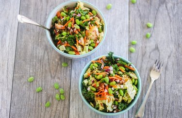 two kimchi salads in blue bowls on wooden surface