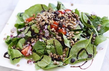spinach lentil salad with tomatoes on a white plate