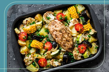 Healthy sheet-pan dinner with baked chicken breast and tomatoes, Brussels sprouts, cauliflower and corn