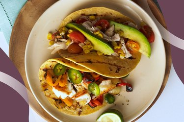 Turkey Tacos with avocado and lime on a wooden plate