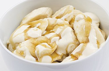 Peanut butter Greek Yogurt and Banana Parfait in white bowl
