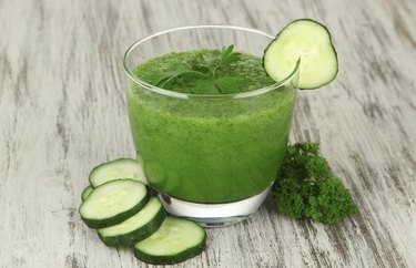 Anti-inflammatory drink Sweet Green Juice in a glass with cucumber wedges