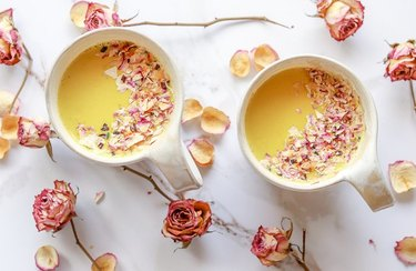 Anti-Inflammatory Turmeric Latte in white mugs with scattered rose petals