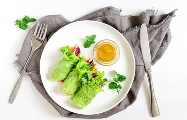 Mango and Black Bean Lettuce Wraps Breakfast Burrito on a white plate with yellow dipping sauce and utensils