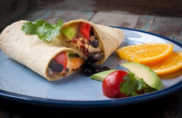 Breakfast Egg Burrito on a blue plate with tomato, avocado and orange wedges