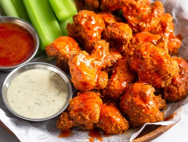 Air Fryer Veggie Buffalo Cauliflower with celery sticks and red and white dipping sauces