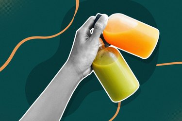 close up of hand holding glass bottles of green and orange juice for a juice cleanse on a dark green background