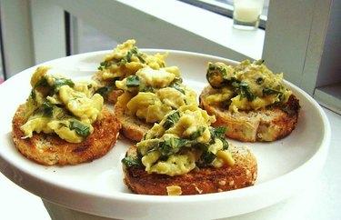 Breakfast-for-Dinner Herb Scrambled Egg Crostini on a white plate