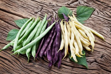 Purple, green and yellow beans lying on a wooden table