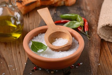 iodine-rich iodized salt in a wooden bowl on table with wooden spoon