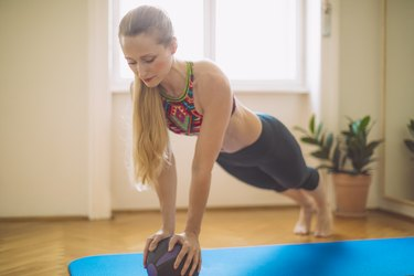 woman doing medicine ball ab exercises at home on a blue yoga mat