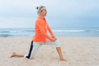 Woman over 50 doing lunge stretch on the beach