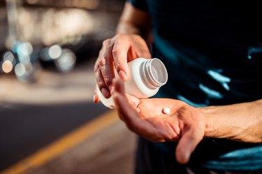 Close up of hands taking a vitamin or supplement from bottle