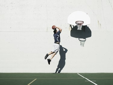 mid-air view of man dunking a basketball after learning how to increase your vertical jump