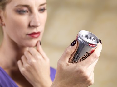 Woman reading ingredients list on a diet soda can