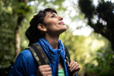 Young woman hiking in a forest, as a way to cope with chronic fatigue syndrome