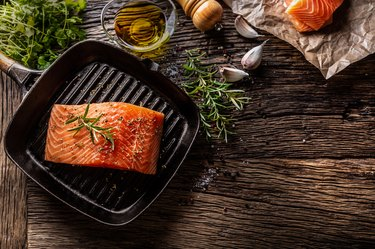 Raw salmon steak in grill pan with salt, pepper, rosemary, olive oil and garlic on rustic oak table.