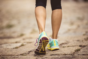 Young fitness woman hiker legs walking on trail