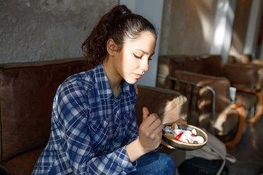 Woman eating breakfast of yogurt and fruit, dark background