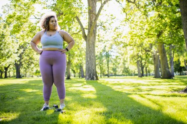 Young woman resting while working out with hand weights outdoors, doing the best strength exercises for beginners with obesity