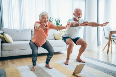 older man and woman doing squat exercises in living room