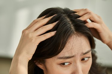 Asian person assigned female at birth running fingers through her hair with a concerned expression wondering why does my hair hurt