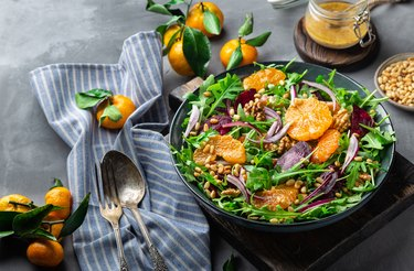 Fresh homemade tangerine and beet salad with arugula, walnuts and pine nuts on grey concrete background with dressing and ingredients