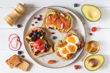 Assorted avocado toasts on white plate with ingredients on the side