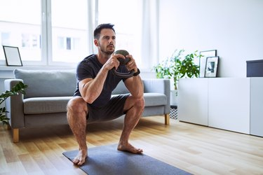 Fit man exercising at home doing kettlebell squat in living room