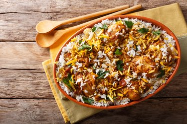 Delicious homemade biryani with chicken, onion, lemon, spices and cilantro close-up. horizontal top view