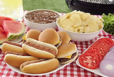 Gluten free buns with hot dogs and hamburgers on summer picnic table