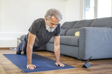 Mature Man Stretching at Home on Exercise Mat