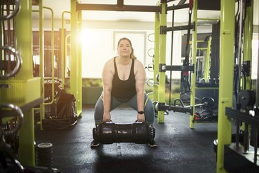 Woman performing sumo deadlift exercise modification with a sand bag in a gym