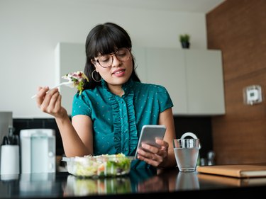 Young businesswoman eating salad in lunch room and using phone