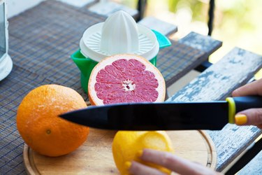 Woman cutting citrus fruits on wooden picnic table with a juicer