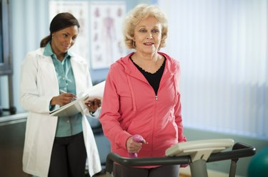 older woman with COPD walking on a treadmill while a doctor takes notes